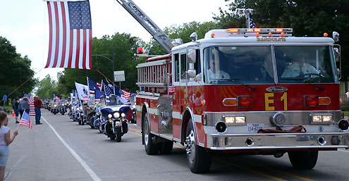 Fire Department ladder truck with flag on ladder in a parade